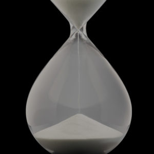 Photo of sand pouring in an hourglass